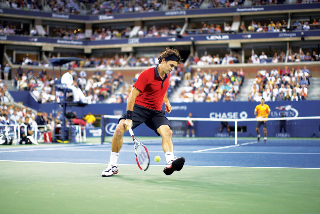 "Federer demonstrates his legendary ""tweener"" shot against Novak Djokovic in the semi finals of the 2009 US Open (Image © Getty Images)"