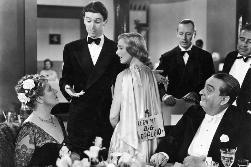 American actor James Stewart (1908 - 1997) introduces American actor Jean Arthur (1900 - 1991) (left) to his mother, played by British actor Mary Forbes (1883 - 1974), while Australian actor Robert Greig (1879 - 1958) looks on in a restaurant scene from director Frank Capra's screwball comedy, 'You Can't Take It With You.' Arthur wears a sign pinned to her cape (Photo by Columbia Tristar/Getty Images)