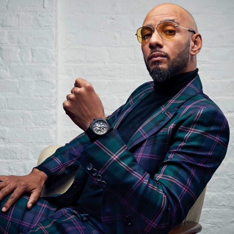 Swizz Beatz wearing the Zenith Defy El Primero 21 with cermacised aluminium case and black rubber strap with alligator-leather coating. Double-breasted multi mauve tartan suit, Bally; black wool roll-neck, John Smedley; aviator sunglasses, Grey Ant
