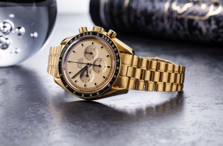 1969 Yellow Gold Omega Speedmaster Tribute to Apollo XI Reference BA 145.022 with a black service bezel insert (© Revolution)
