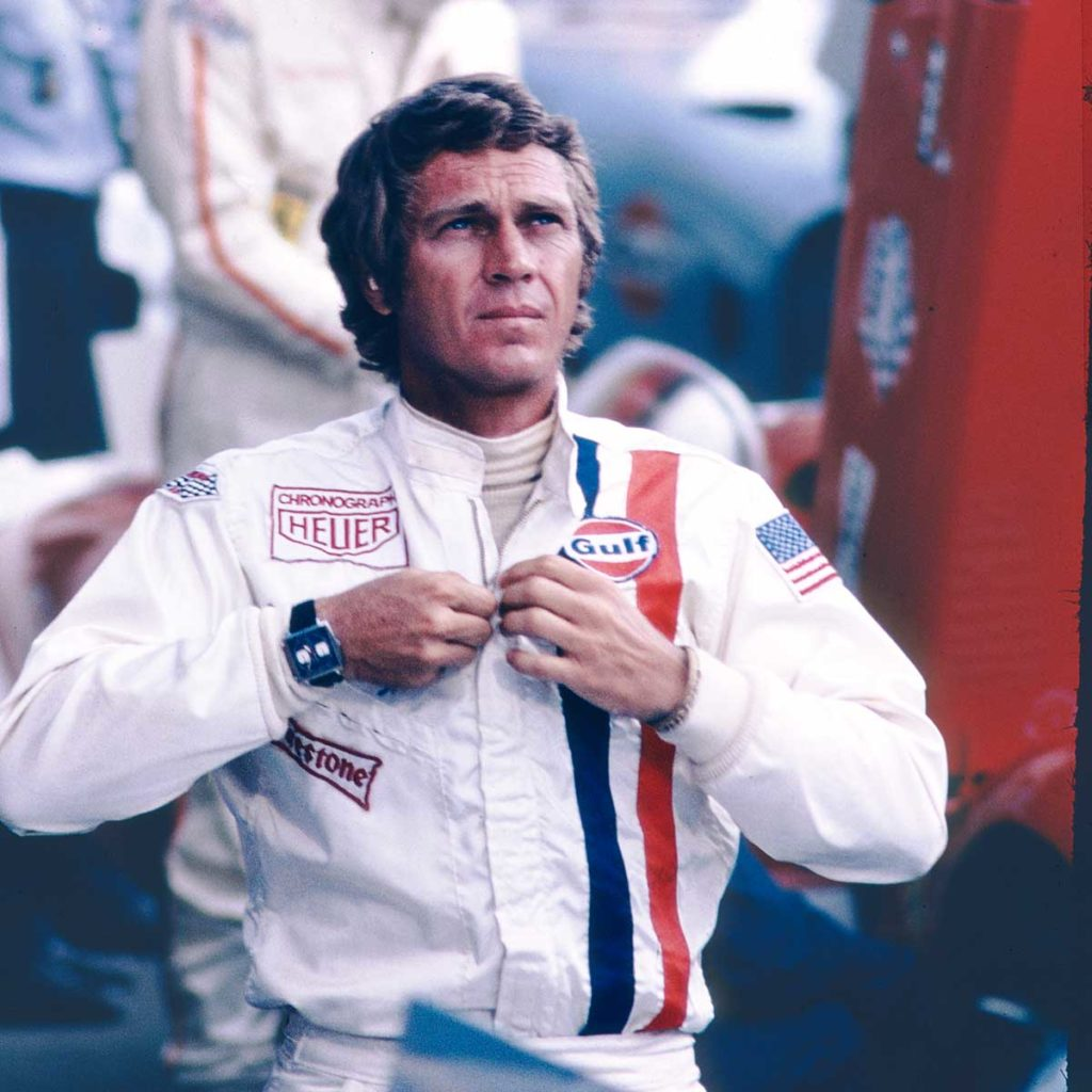 "American actor Steve McQueen in the 1971 film, ""Le Mans"" where he played the part of racing driver, Michael Delaney. On his wrist, clearly visible is the four-sided TAG Heuer Monaco with the iconic blue dial"