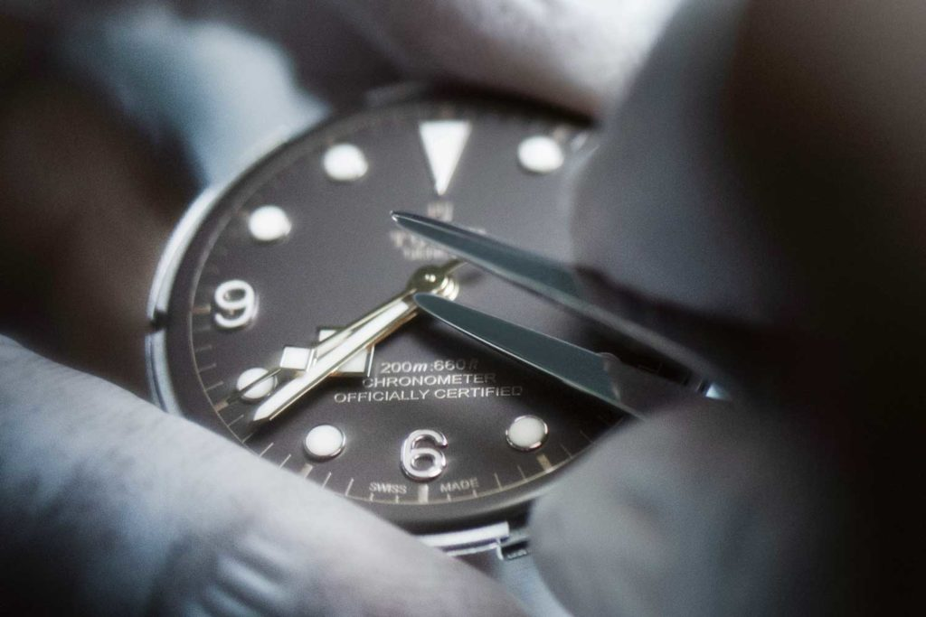 Watchmaker testing functions after the dial and hands have been assembled