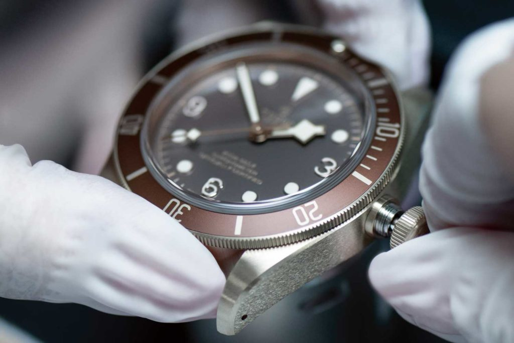 Watchmaker testing alignment of hands after complete assembly of the case