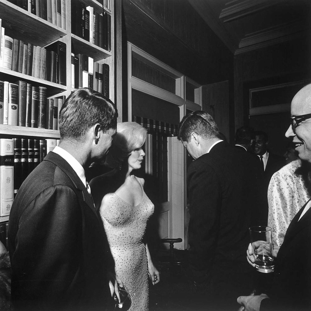 Marilyn Monroe stands between Robert Kennedy (left) and John F. Kennedy at a party in New York, following the democratic fundraiser at Madison Square Garden where Monroe famously sang Happy Birthday to JFK
