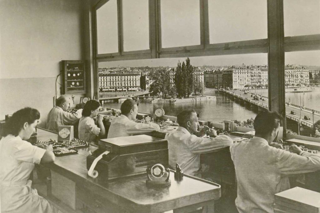 A historical image of Patek Philippe's watch atelier. The brand maintains this atelier even today, with watchmakers working with a grand view of the Lake Geneva