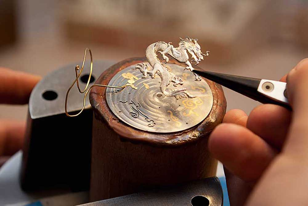 Cloud swirls of precious metal are hammered into place around an engraved dragon