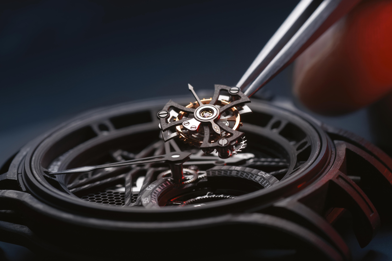 A watchmaker sets a Roger Dubuis tourbillon into a multi-layered carbon case (Image © Revolution)