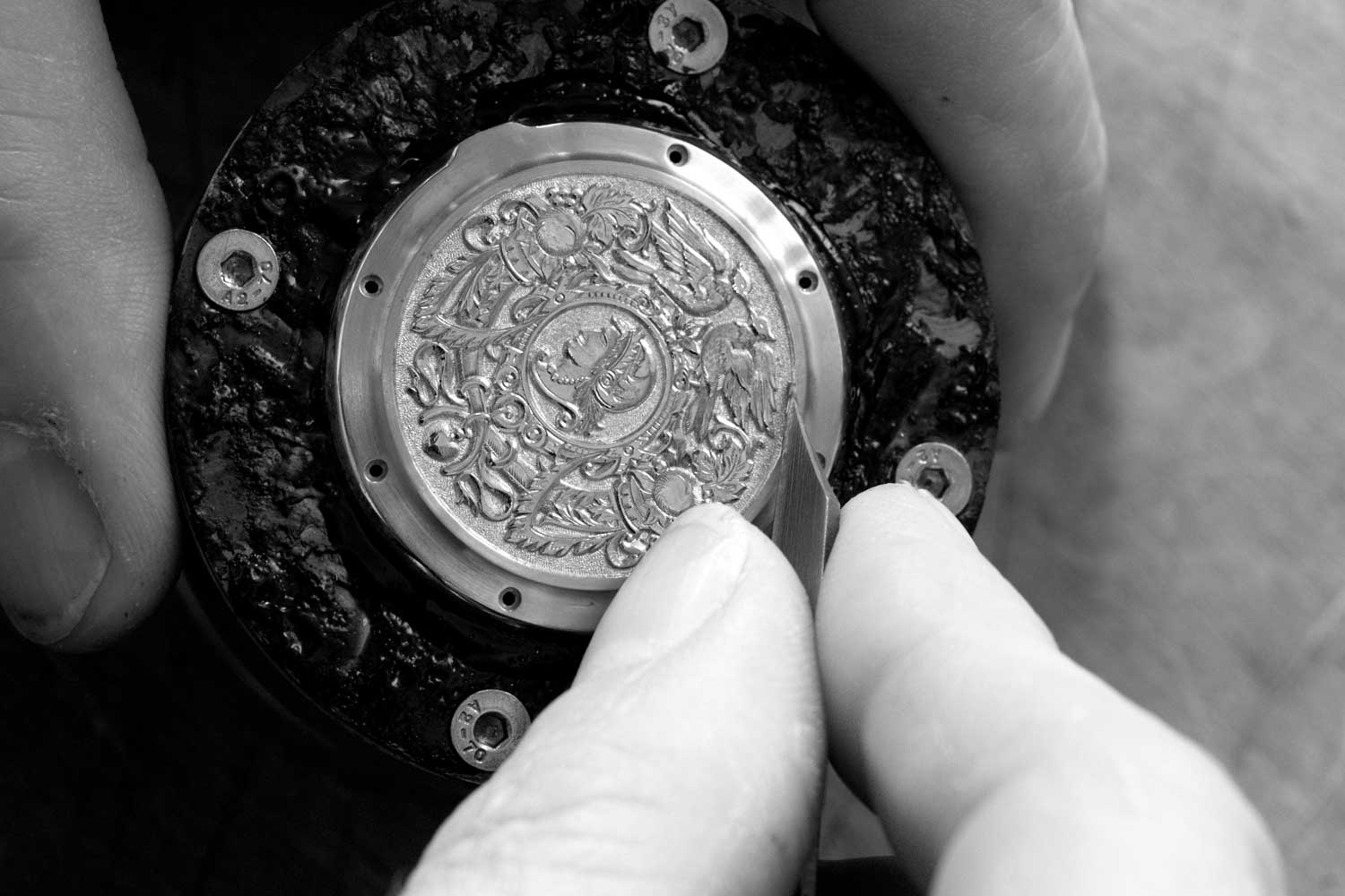 A personalized Lange watch is fitted with a precious metal back that displays an engraved motif
