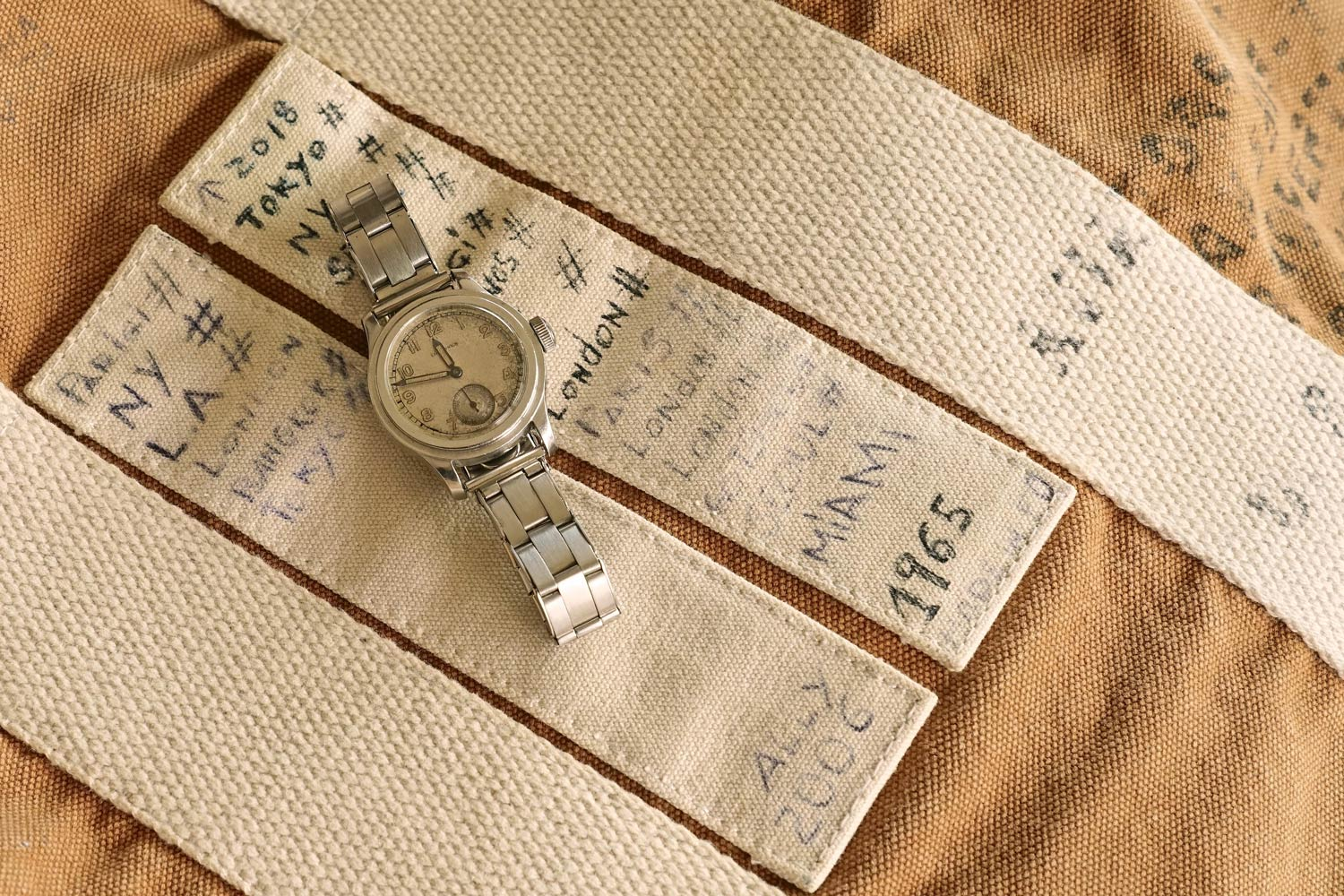 "Steel waterproof Longines ""Tre Tacche"" ref. 3864, with silvered dial and luminous Arabic numerals, cal. 12.68Z, 1942. Canvas travel bag with the Alessandro's travel dates around the world"