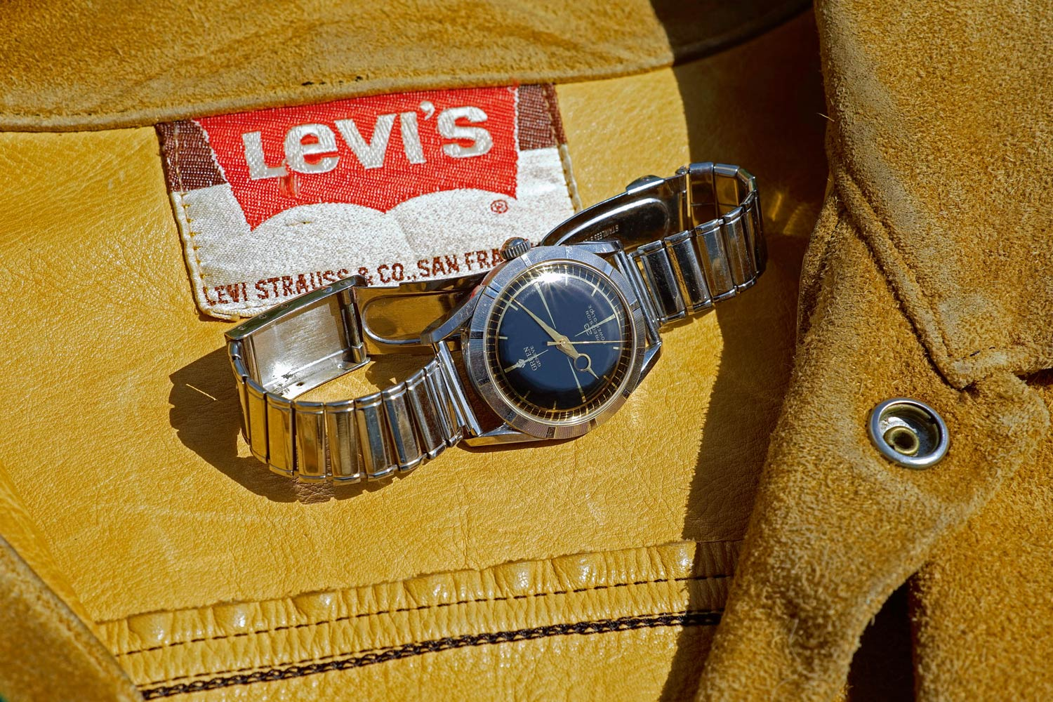 Steel self winding Gruen 23 Precision, Power-Glide with black gilt dial and ridged bezel, 1958. Vintage suede Levi's jacket, '60s
