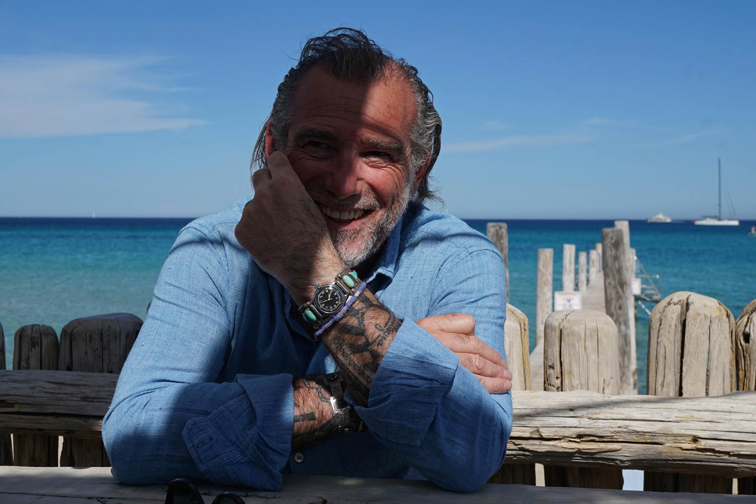 Alessandro Squarzi at Club 55, St. Tropez, wearing a military Elgin wristwatch, 1945, with silver and turquoise Navajo bangle. Vintage chambray shirt