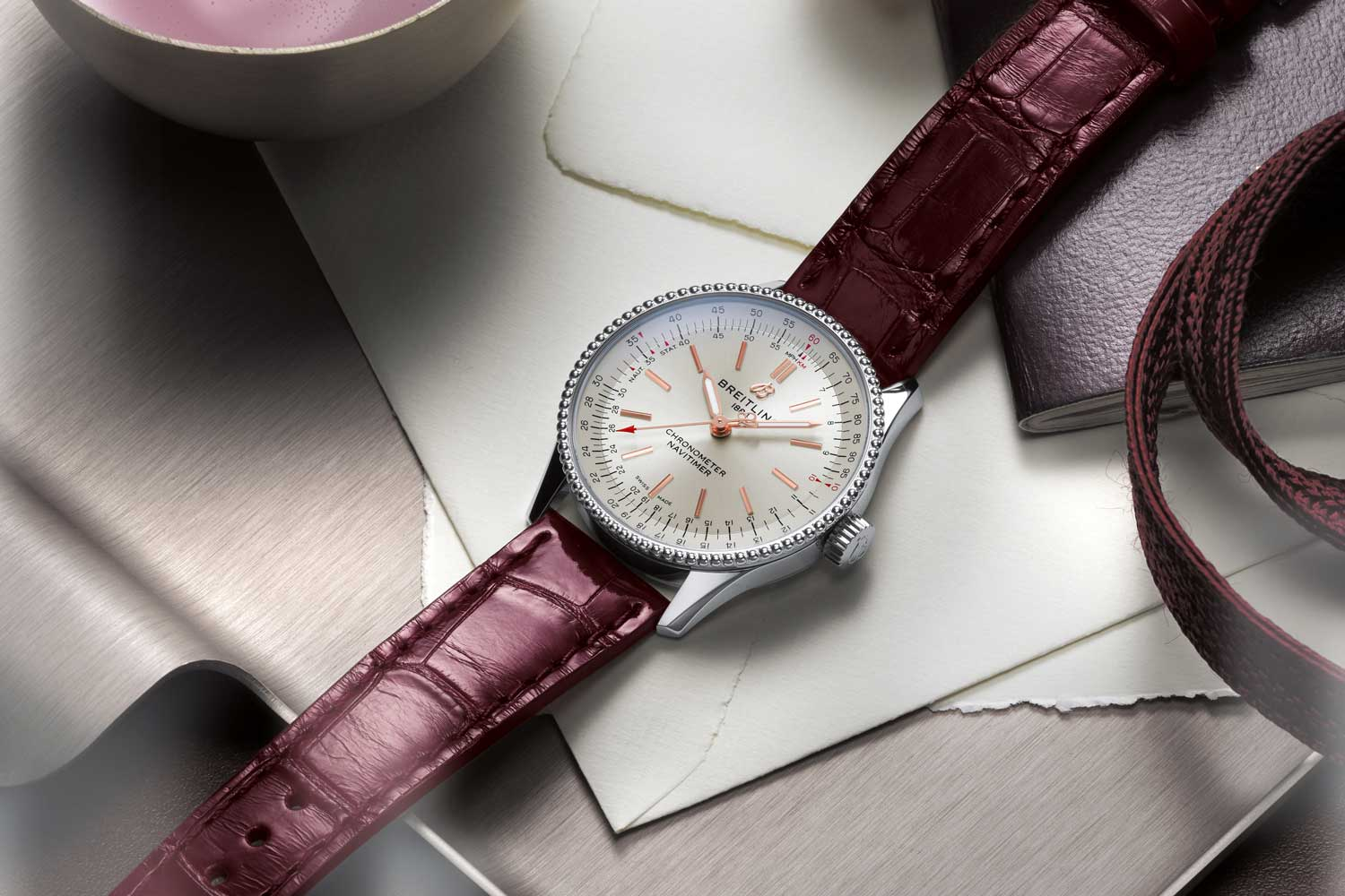 Navitimer Automatic 35 with a silver dial and a burgundy alligator leather strap