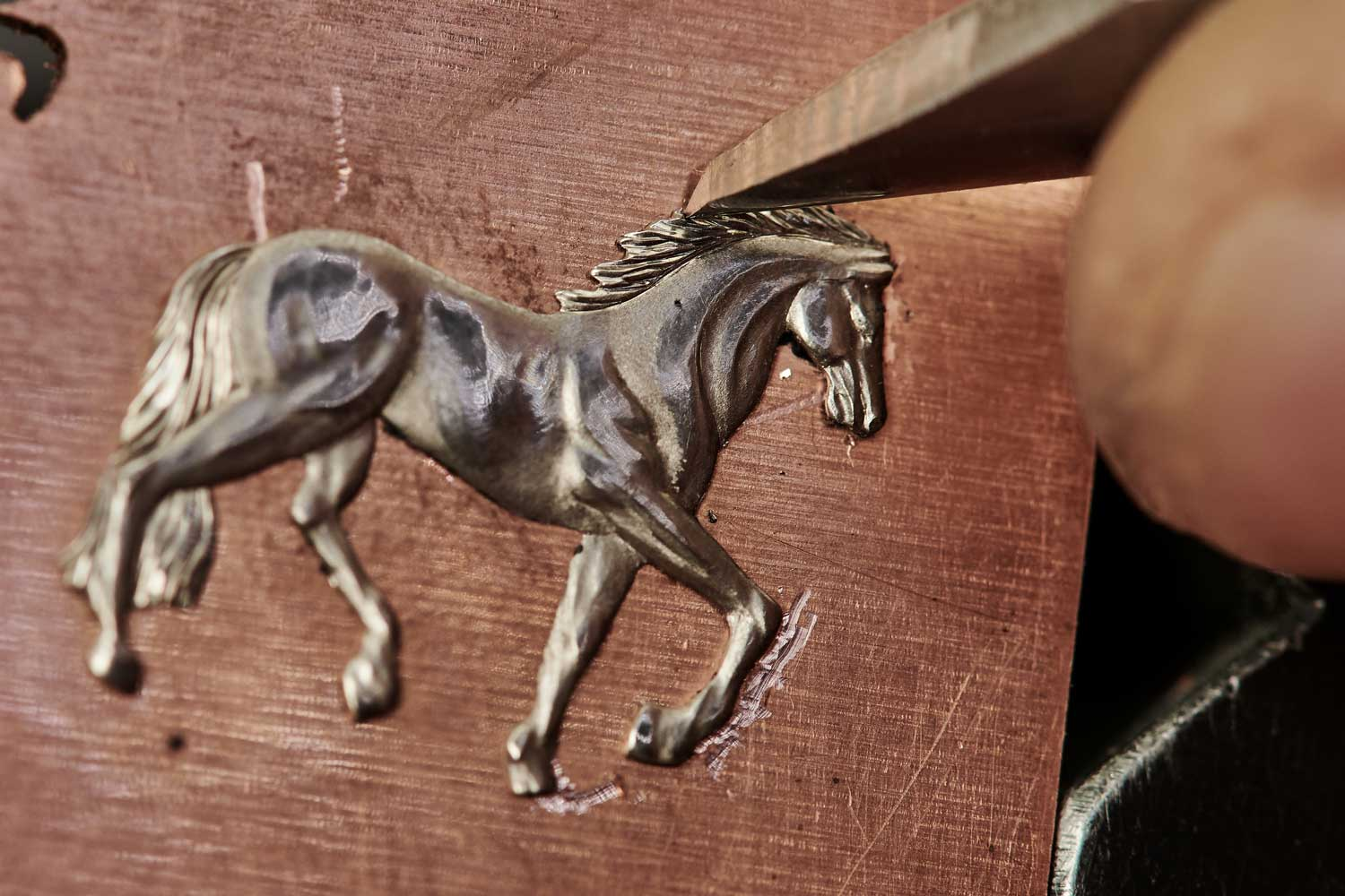 The engraver carves each relief detail by hand, taking nearly a week for each dial.