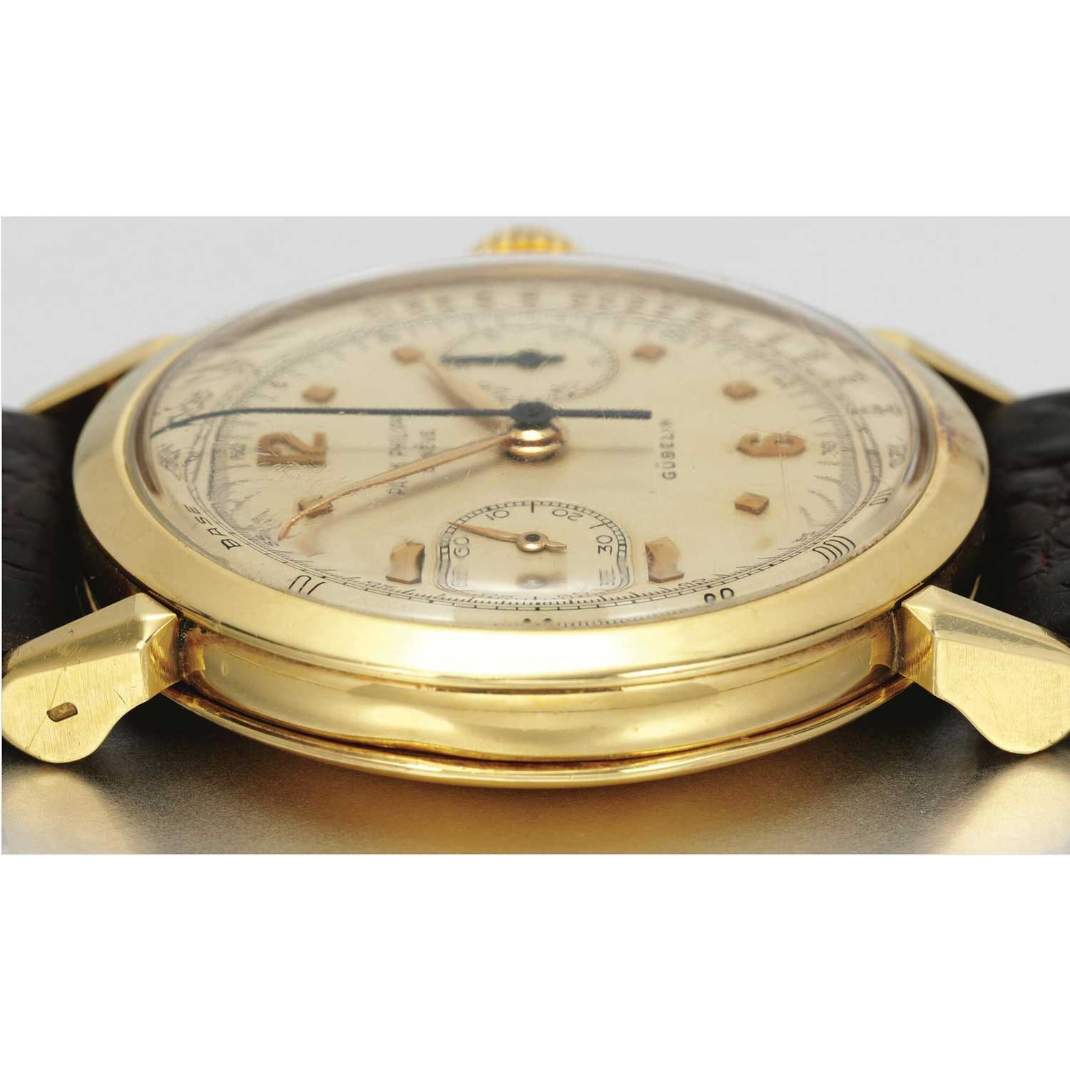 Case side of the 1953 Patek Philippe ref. 1579 yellow gold chronograph with silvered dial, applied gold faceted square and Arabic numerals, retailed by Gübelin (Image: Sothebys.com)