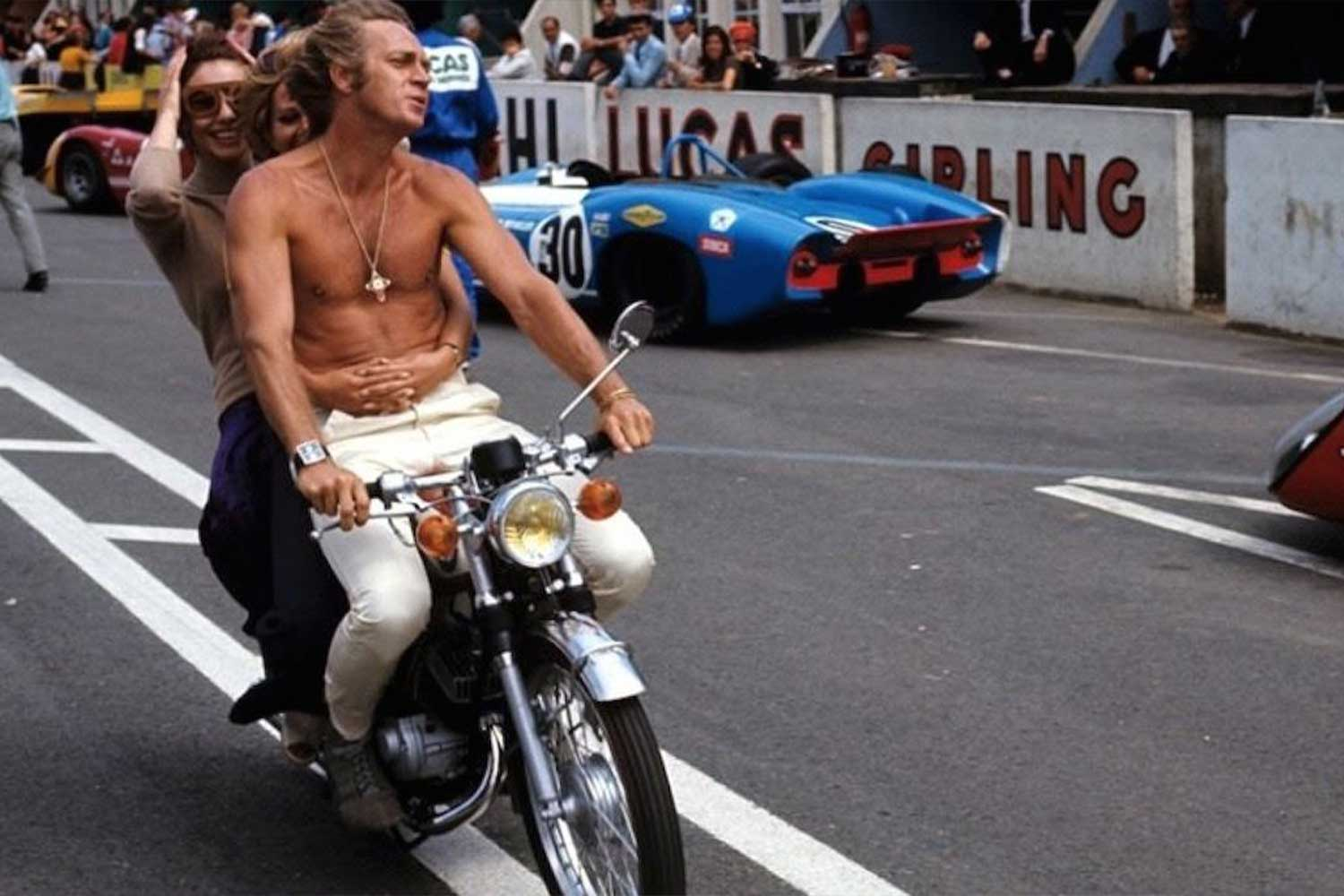 Steve McQueen out and about on the set of Le Mans on a motorbike, wearing the Heuer Monaco on his right wrist