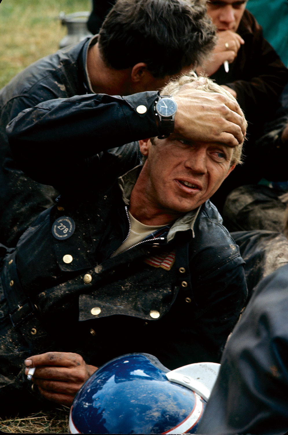 Steve McQueen resting after his run out on the 1964 ISDT track, a cigarette in his hand, the other resting on his forehead. Each evening after the race (300km on average, on terrible paths), the runners collapse in the grass, covered in mud and oil. (Photo by Francois Gragnon / Paris Match via Getty Images)