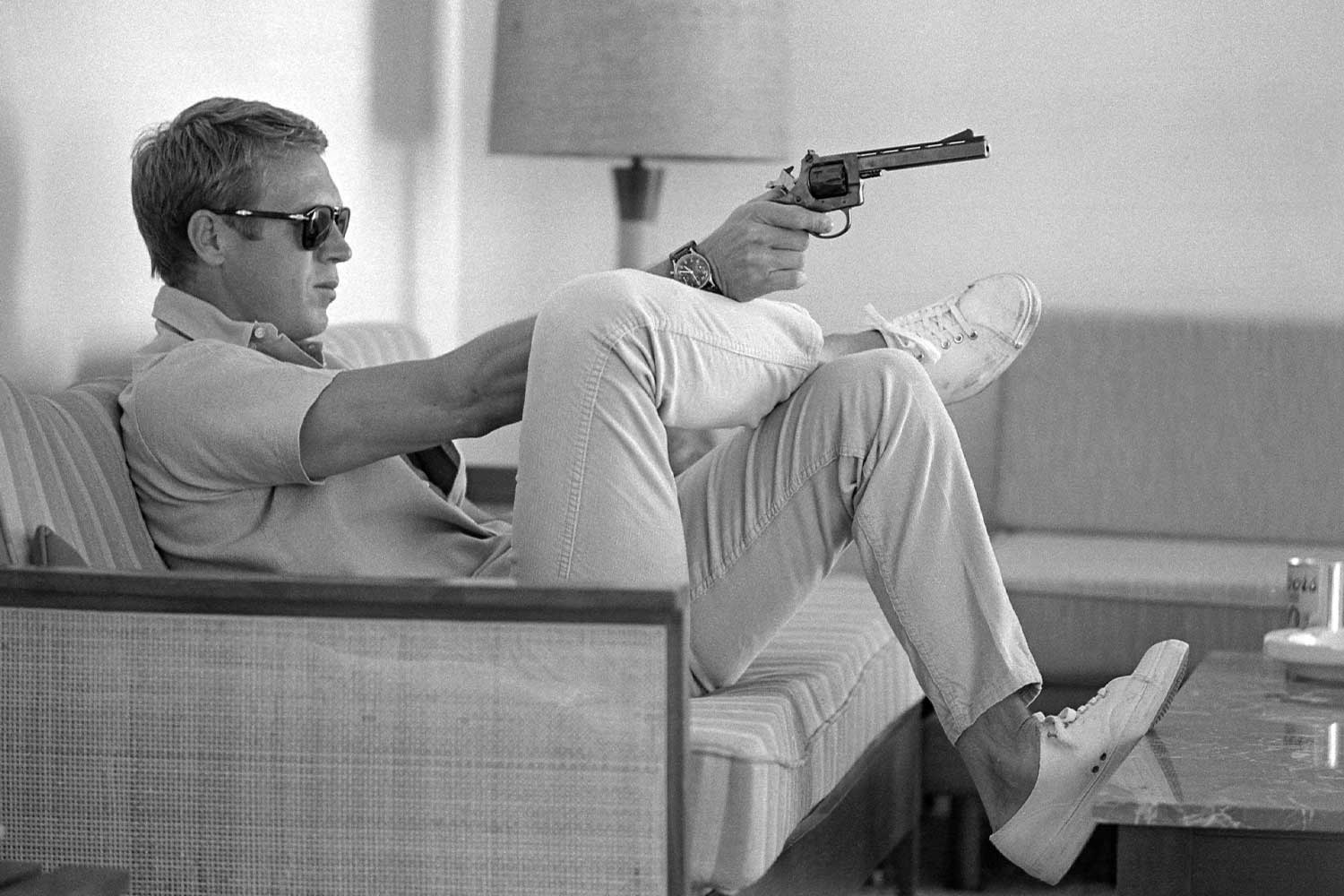 Profile view of Steve McQueen as he sits on a sofa in his home, sunglasses over his eyes, as he aims handgun, his wrist balanced on his crossed leg, Palm Springs, California, May 1963. (Photo by John Dominis/The LIFE Picture Collection via Getty Images)