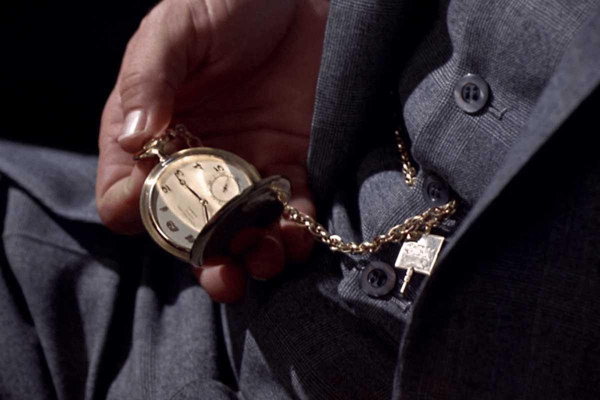 Crown checks his gold Patek Philippe pocket watch