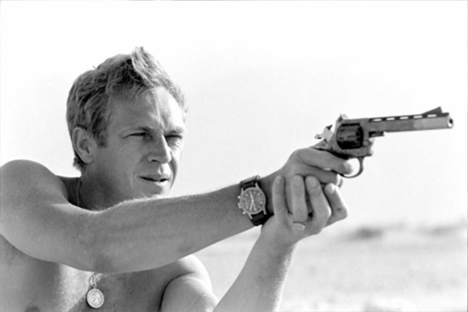Steve McQueen holding a pistol and taking aim in a desert area around Palm Springs, California June 1963 (Photo by John Dominis/The LIFE Picture Collection via Getty Images)