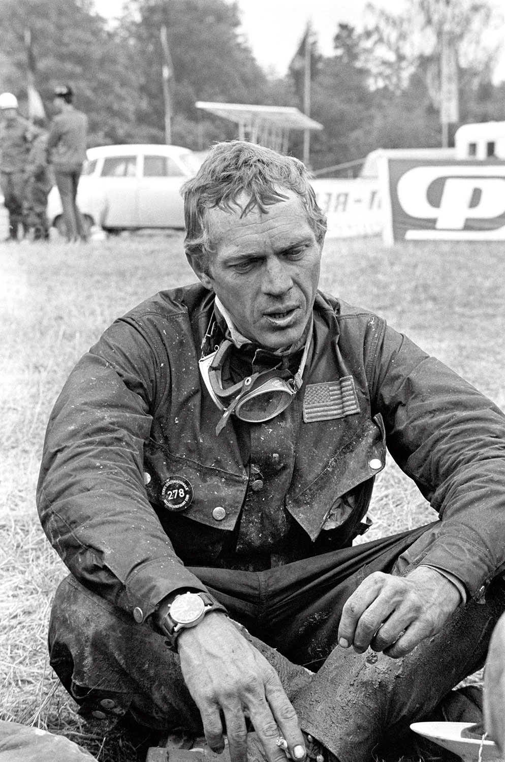 Steve McQueen resting after his run out on the 1964 ISDT track. Each evening after the race (300km on average, on terrible paths), the runners used to collapse on the grass, covered in mud and oil. On his wrist visible is the Hanhart 417 ES (Photo by Francois Gragnon / Paris Match via Getty Images)