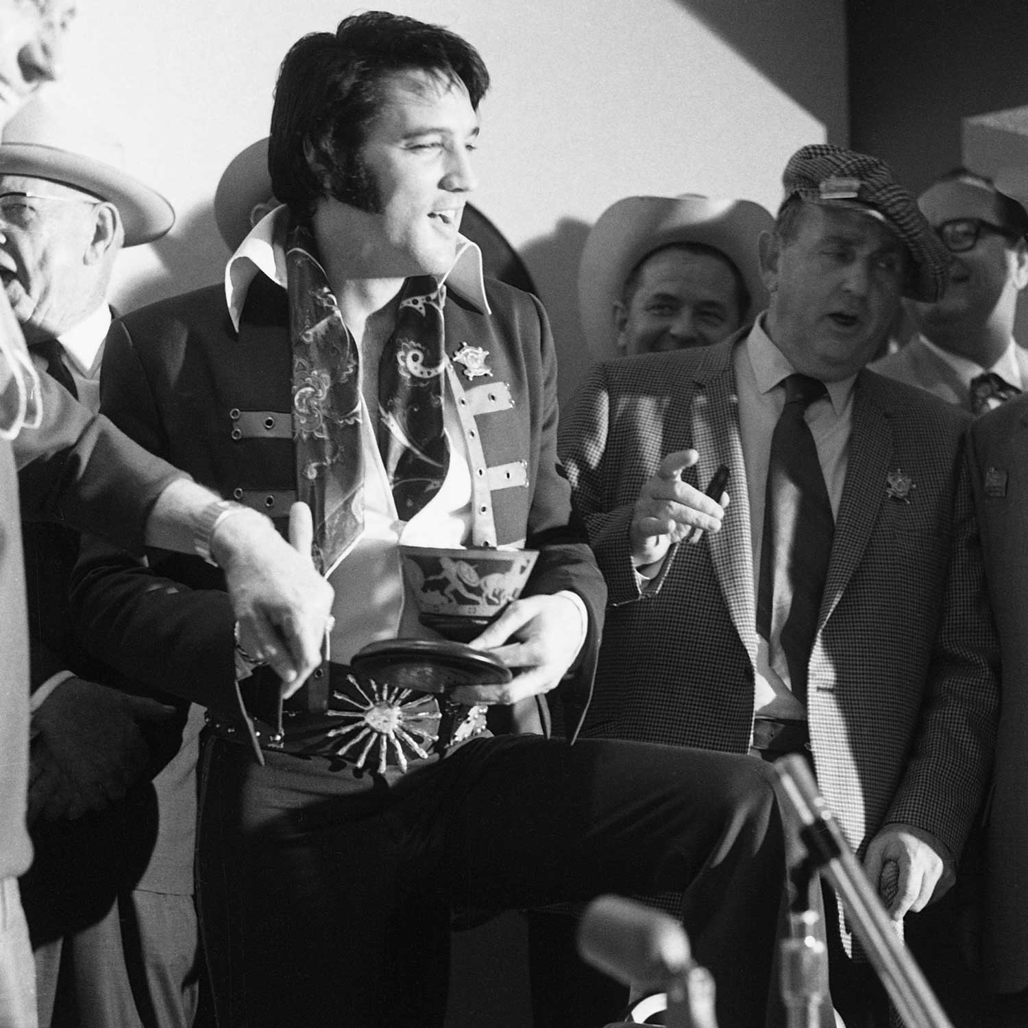 Elvis Presley is presented with the Rolex King Midas for his Houston Astrodome Livestock Show and Rodeo concerts. He's seen here holding the urn-shaped box, with the watch seen on his left (Photo by Silver Screen Collection/Getty Images)