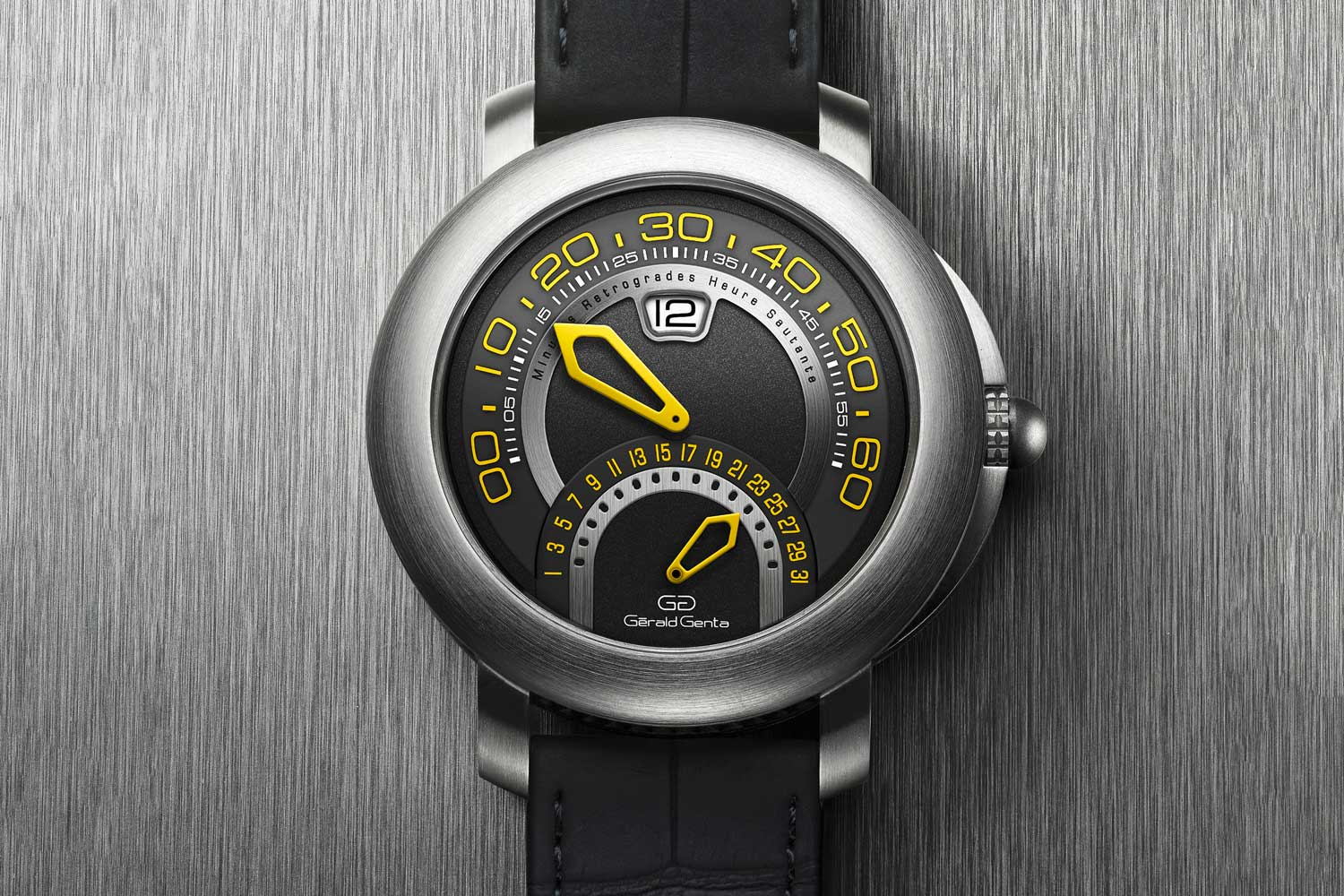 """Yellow numerals and hands add an unexpected flash of color against the anthracite dial. A matte black alligator strap with titanium buckle offers an extra layer of """"chic"""" to an otherwise sporty wristwatch."""