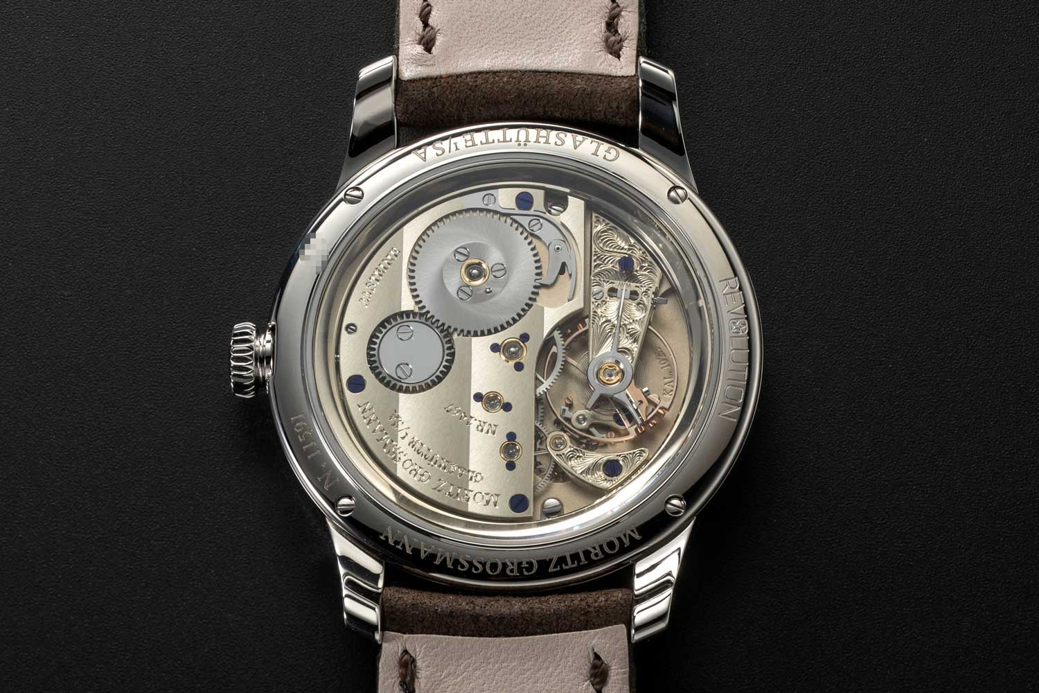 The Moritz Grossmann Benu 37 Steel with Grand Feu Enamel Dial for Revolution & The Rake is powered by the Manufactory calibre 102.1 which is forged in untreated German silver and decorated with wide Glashütte ribbing over the expansive three-quarter plate, marked with gold chatons and annealed brown-violet screws (©Revolution)