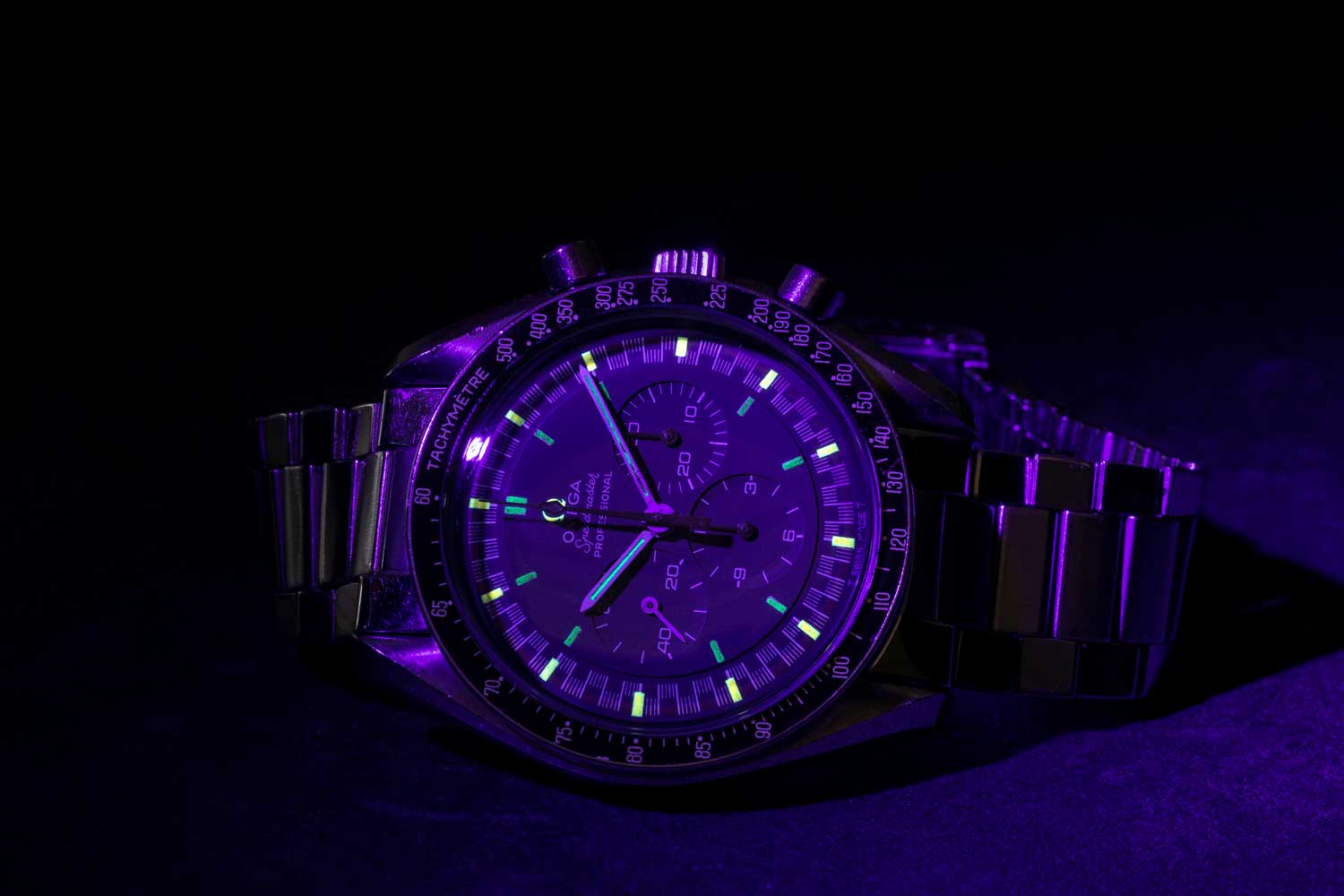 Revolution's Speedmaster Reference 145.022-69 with the Racing Dial and orange arrow-tipped central chrono hand aglow in the dark, under a UV light (©Revolution)