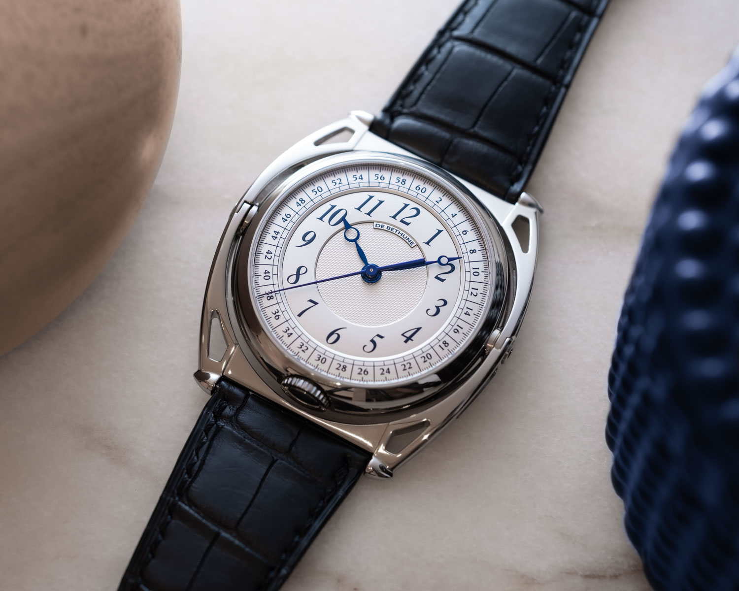 The alternate side of the two-sided De Bethune DB Kind of Two Tourbillon showcases a more classic face with hand-polished and blued titanium hands for hours, minutes and seconds