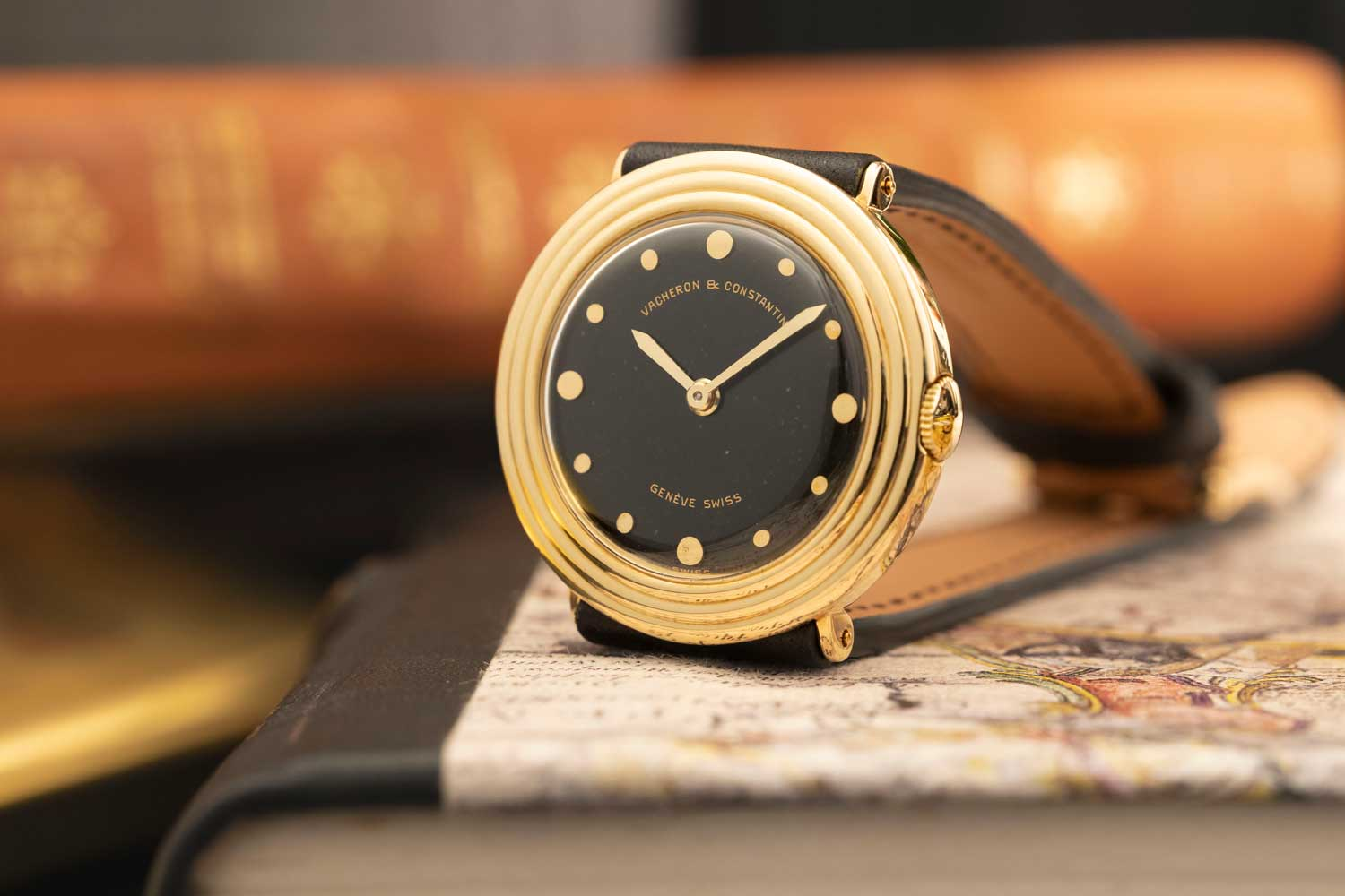 """1948: Altesse Reference 3681 30mm in diameter; 18K yellow gold round-shaped wristwatch; Gadrooned bezel; black """"Duco"""" laquered dial, 12 dots in yellow gold, larger at 3, 6, 9, and 12 o'clock; gilt signatures in a form of an arc """"Vacheron & Constantin"""" at 12 o'clock, and """"Genève Swiss"""" at 6 o'clock. Sword-shaped hands in yellow gold (©Revolution)"""