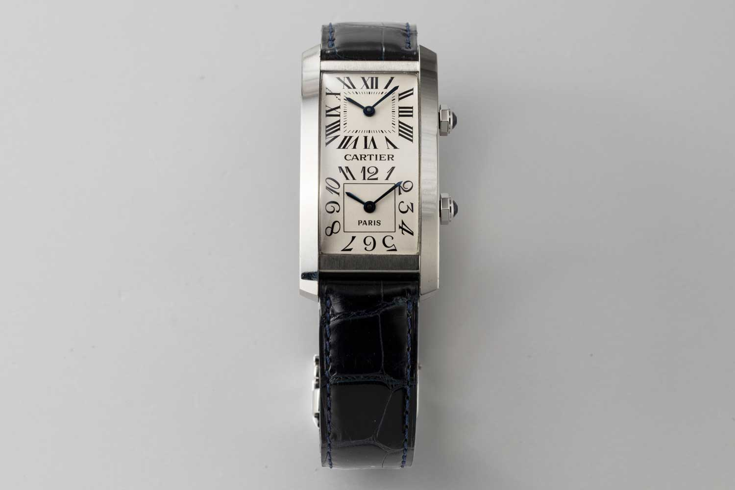 """1996 No. 1/1 Cartier Paris Tank Cintrée in platinum with faceted sapphire-set winding-crown; double white gold dial with Roman chapters for home time and Arabic numerals for local time, blued steel """"glaive"""" hands; two rhodium plated 6 3/4""""' two movements, Cartier Caliber 067; this particular example is from the private collection of Auro Montanari (©Revolution)"""