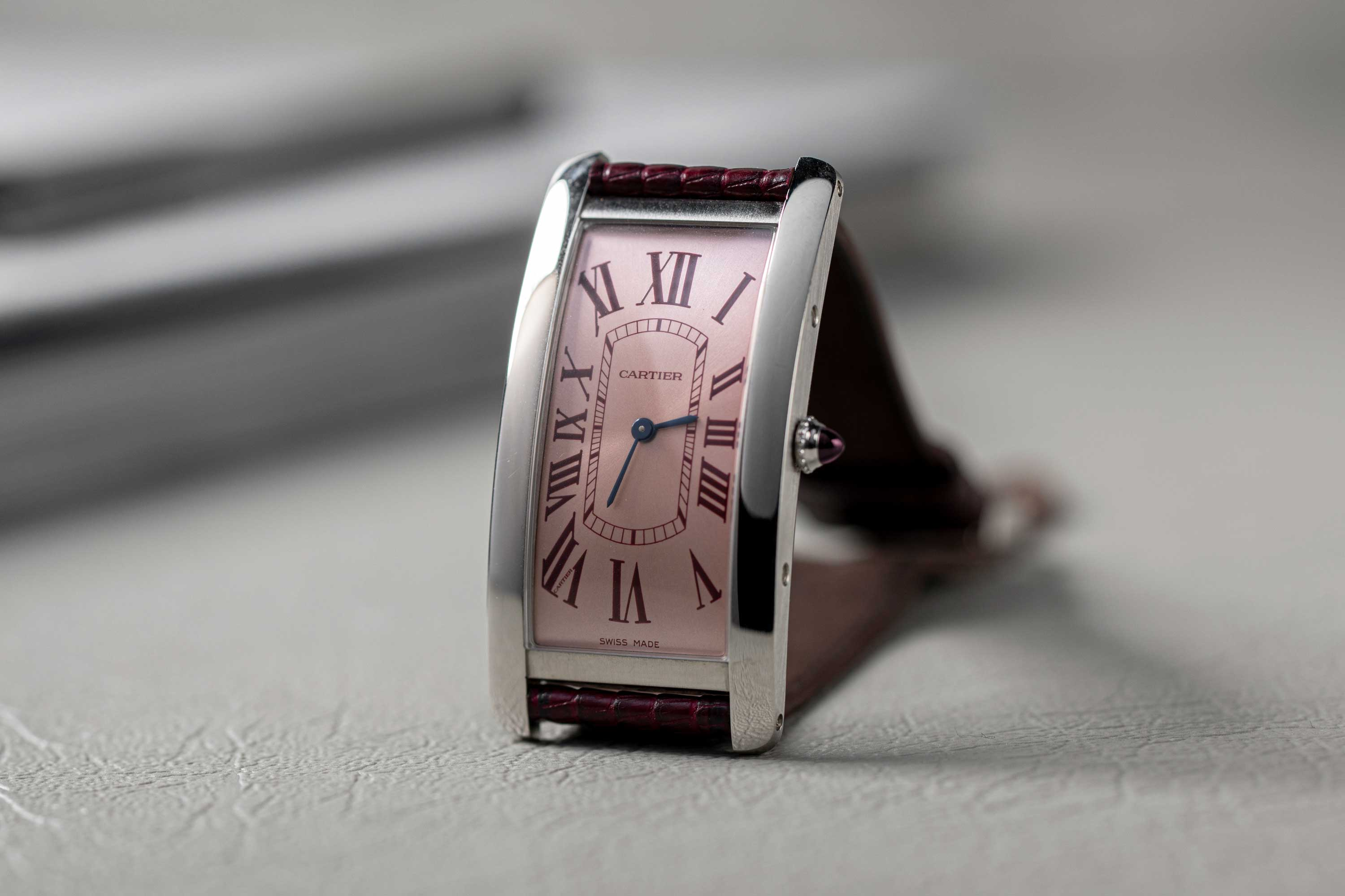 Wei Koh's special order Cartier Tank Cintrée in platinum with a salmon dial and burgundy Roman numerals, fitted on a burgundy lizard strap made by Federico De Peppo of Huitcinq1988 (©Revolution)