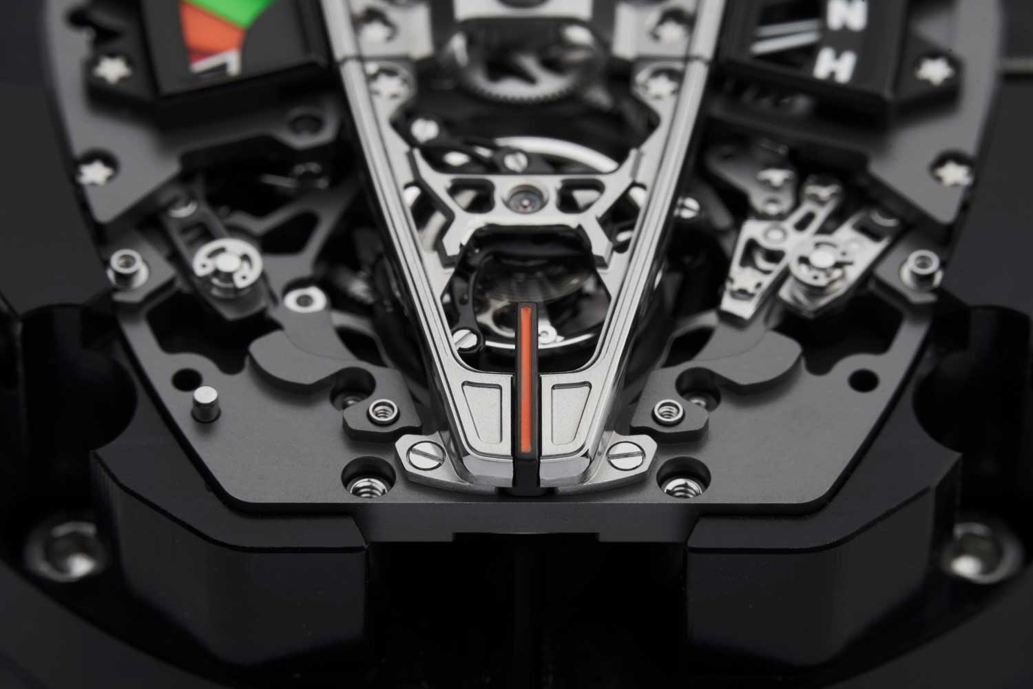 The orange line running from the lower part of the movement and onto the strap comes from the vertical stoplight mounted in the Speedtail's rear screen