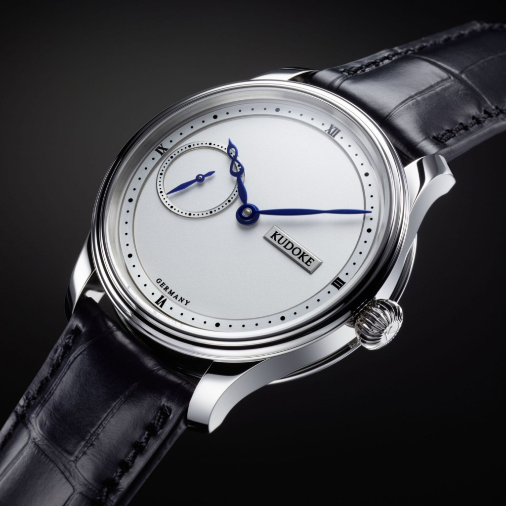 The Kudoke 1 dial is a frosted white two-layer design with Roman numerals and dots in a clean outer chapter and elegant blued steel hands with the infinity sign worked into the shape.