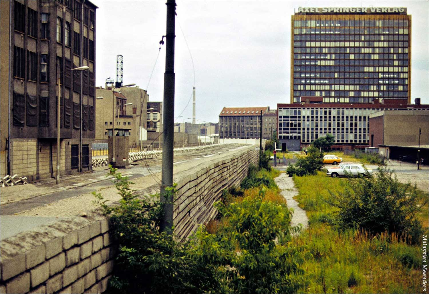 Caption by Photographer: East Berlin on the left and West Berlin on the right; in 1959-1960, Springer moved its headquarters from Hamburg to West Berlin as a symbolic protest over the division of Germany. The office building is on the right side of the above photo abutting the Berlin Wall separating it from East Berlin on the left side of the photo. Note that there's another Soviet watch tower. No one is allowed to escape, and if they try, there's a wide no-man's-land where the guards have a clear shot (Image: malaysianmeanders.blogspot.com)