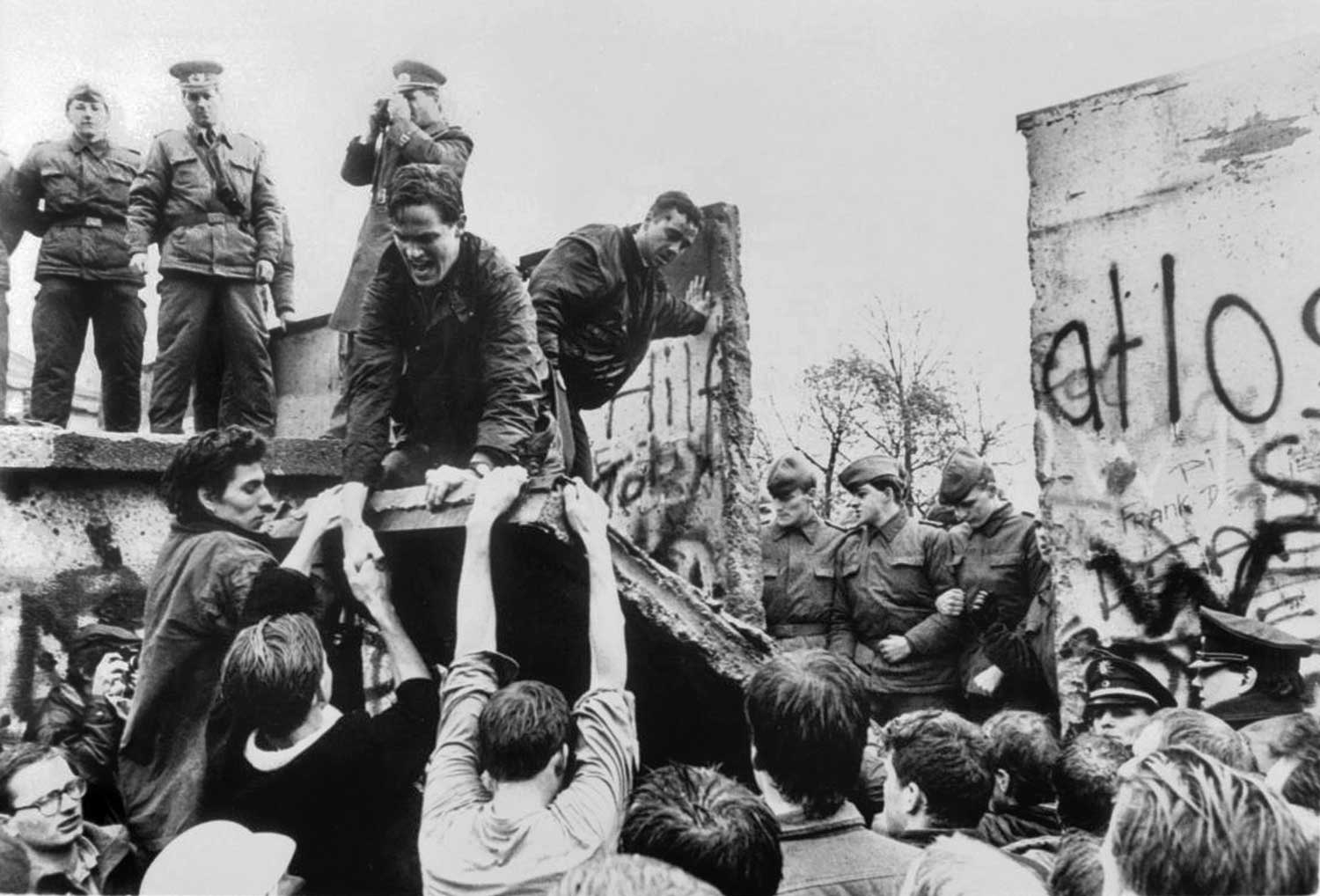 West Berliners tearing down part of the wall as East German guards looked on, on Nov. 11, 1989.Credit...Keith Pannell/Mail on Sunday, via Reuters
