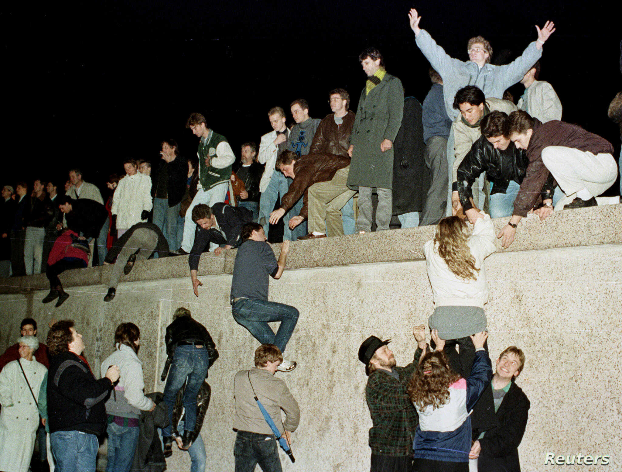 East German citizens climb the Berlin wall at the Brandenburg Gate as they celebrate the opening of the East German border in this November 10, 1989 file photo (Image: voanews.com)