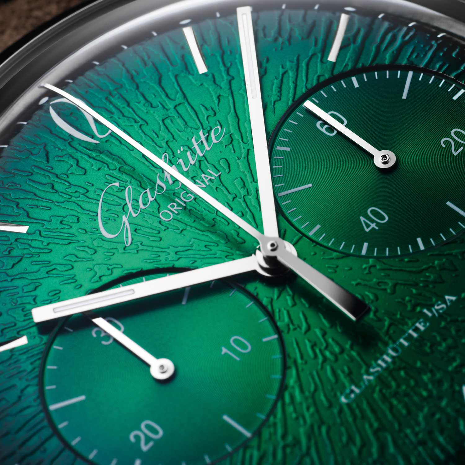The raised guilloche effect on the dial is achieved by means of a 60-ton press which impresses the eye-catching effect onto a brass blank.