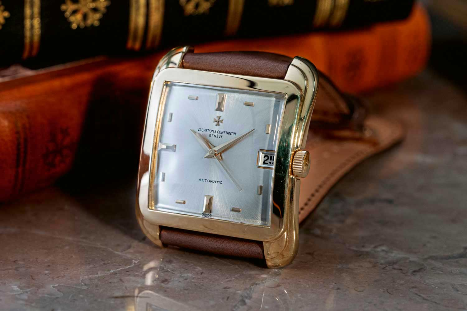 Vacheron Constantin Cioccolatone Reference 6440Q from 1967. The square-shaped 18K yellow gold automatic wristwatch has a silvered sunray-satined dial, indexes in gold, date aperture at 3 o'clock, center seconds (©Revolution)