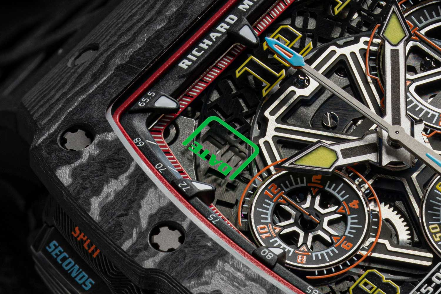 The dial of the RM 65-01 features the hour and minute hand, hour indexes and small seconds are all rendered yellow; the chronograph 12-hour counter at nine o'clock and the 30-minute counter at three o'clock are both in orange, as is the chronograph seconds hand; superimposed on top of the chrono seconds hand is the blue split seconds hand; bottom right, you'll find the gear selector and top left you'll find the date (©Revolution)