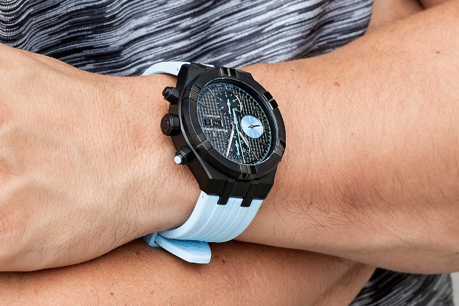 The watch comes on an integrated, light blue FKM rubber strap with a black DLC pin buckle.